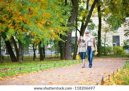Happy young couple enjoying beautiful autumn day - stock photo