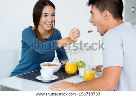 Happy Young Couple Enjoying Breakfast in the kitchen - stock photo