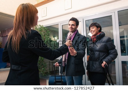 Happy young couple entering in hotel with key of the room. Focus on key. - stock photo