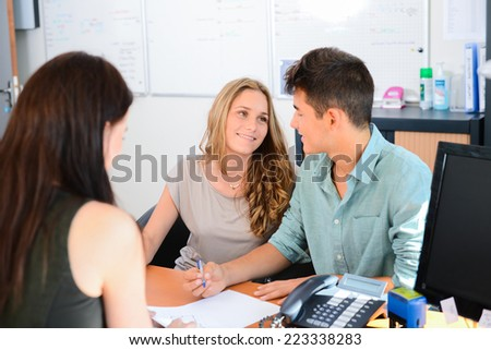 happy young couple getting advice in office with beautiful business woman - stock photo