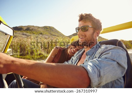 Happy young couple going on holidays together in a open top car. Loving couple enjoying on a road trip. - stock photo