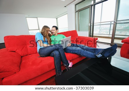 happy young couple have fun and relax at comfort bright apartment and work on laptop computer - stock photo