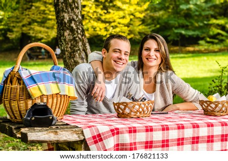 Happy young couple having a picnic and sitting on a park bench enjoying the autumn nature in the park  - stock photo