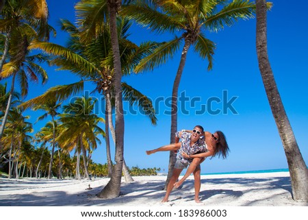 Happy young couple having beach fun piggybacking laughing together during summer holidays vacation on tropical Caribbean beach. - stock photo