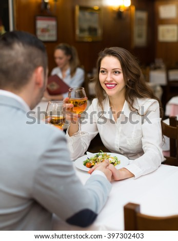 Happy young couple having dinner with champagne in restaurant  - stock photo