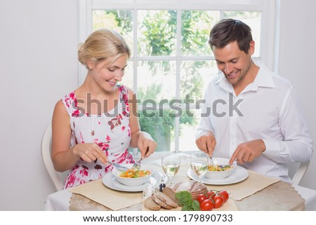 Happy young couple having food at home - stock photo