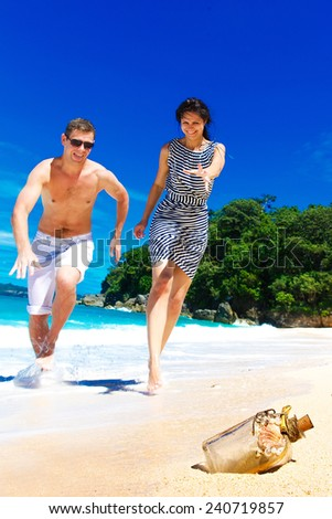 Happy young couple having fun on the shore of a tropical island. Summer vacation concept. - stock photo