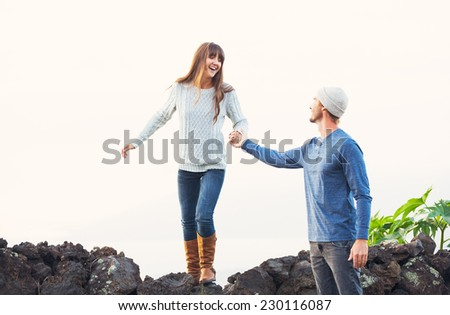 Happy Young Couple Having Fun Outdoors. Man helping attractive girlfriend over rock wall. Chivalry Concept, Romantic Date. - stock photo