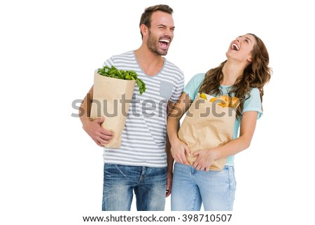 Happy young couple holding bag of vegetables on white background - stock photo