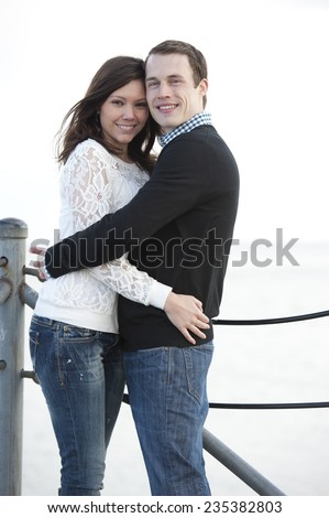 Happy young couple holding each other on a sunny day at the pier. - stock photo
