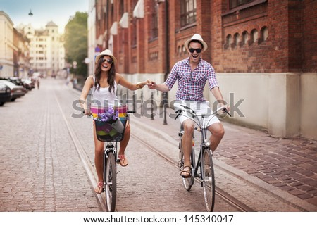 Happy young couple holding hands and riding on bike - stock photo