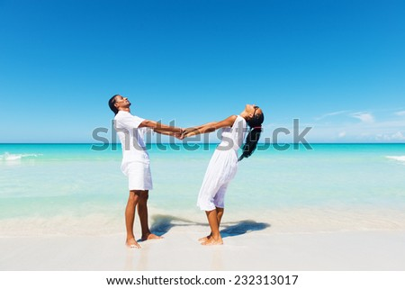 Happy, young couple holding hands at the tropical beach, face to face.Copy space  - stock photo