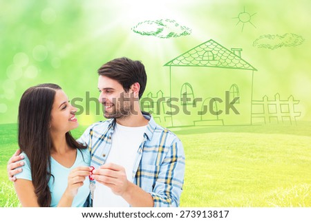 Happy young couple holding new house key against field with glowing sky - stock photo