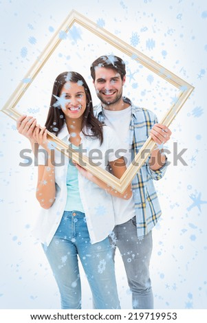 Happy young couple holding picture frame against snow falling - stock photo