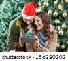 Happy young couple holding present against Christmas tree in store - stock photo