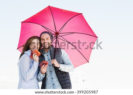 Happy young couple holding umbrella and maple leaves outdoors - stock photo