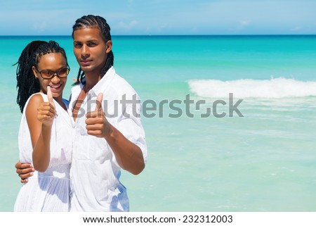 Happy, young couple hugging, thumbs up at the tropical beach.Copy space  - stock photo