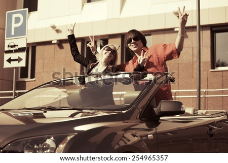 Happy young couple in a convertible car - stock photo