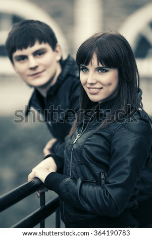 Happy young couple in leather jackets outdoor - stock photo