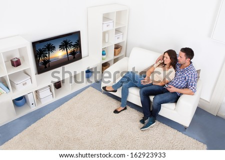 Happy Young Couple In Livingroom Sitting On Couch Watching Television - stock photo