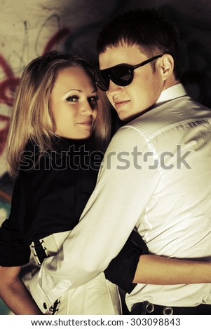 Happy young couple in love at the grungy wall - stock photo