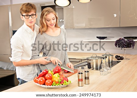 Happy young couple in love cooking a dinner on a kitchen and drink red wine. Healthy food. Happy family. - stock photo