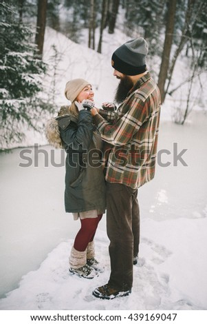 Happy young couple in love cuddling in rustic style in the winter forest - stock photo