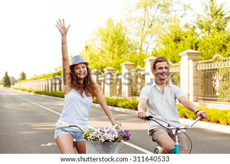 Happy young couple in love cycling - stock photo