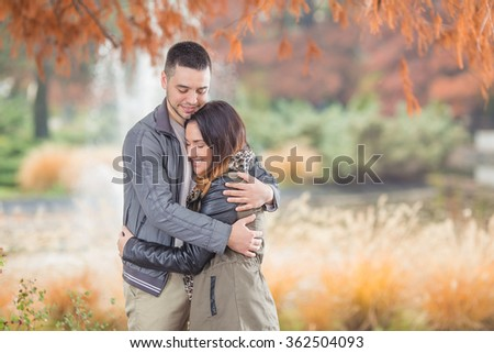 Happy young couple in love embracing while walking in a park - stock photo