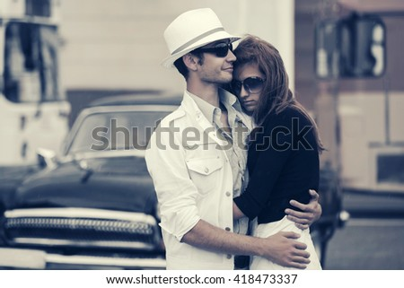 Happy young couple in love. Male and female fashion model outdoor. Man and woman on city street - stock photo