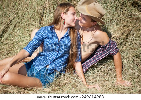 Happy young couple in love on haystack in summer day  - stock photo