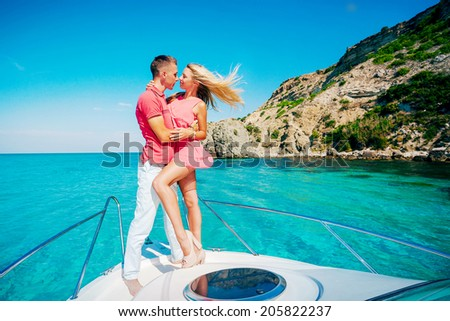 Happy young couple in love relaxing on a yacht at sea. Luxury vacation on the water. - stock photo