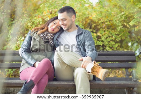 Happy young couple in love sitting on a park bench - stock photo