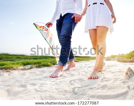 Happy young couple in love with flying a kite on the beach - stock photo