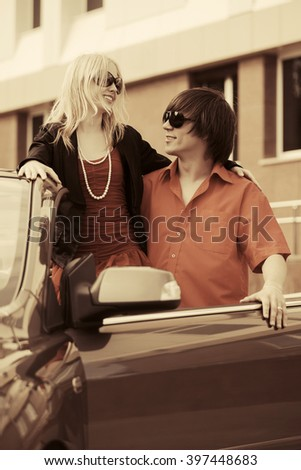 Happy young couple in love with new convertible car - stock photo