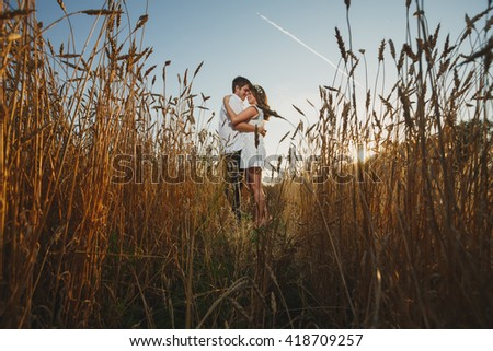 happy young couple in romance and fun wheat field in summer beautiful Ukrainian couple in wheat field Perhaps Russian pair patriotism and love of country Natural natural beauty eco-friendliness - stock photo