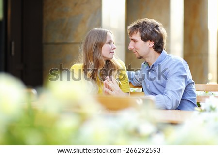 Happy young couple in the outdoor cafe at the summer day  - stock photo