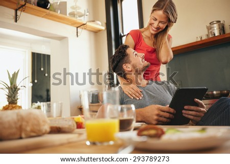 Happy young couple in their kitchen in morning. Man sitting at breakfast table with a digital table with woman standing next to him. Both looking at each other smiling. - stock photo