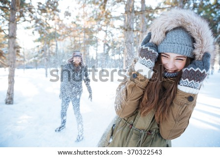 Happy young couple in winter clothes playing snowballs outdoors - stock photo