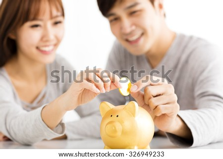 Happy young Couple Inserting Coin In Piggybank   - stock photo