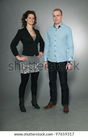 Happy young couple isolated on grey background - stock photo