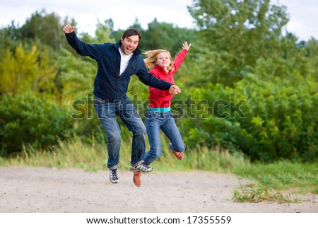 Happy Young Couple - jumping in the sky against a green tree - stock photo
