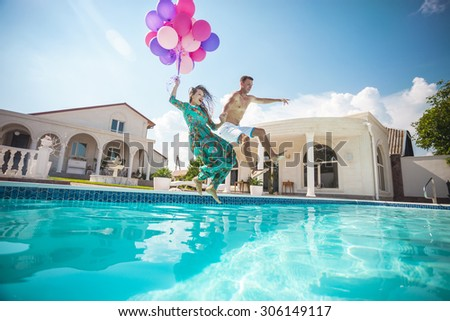 Happy young couple jumping into the pool while holding a bunch of balloons  - stock photo