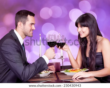 Happy young couple looking at each other while toasting wineglasses at restaurant table - stock photo