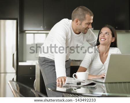 Happy Young couple looking at each other while using laptop in modern kitchen - stock photo