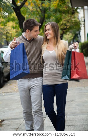 Happy young couple looking at each other while walking on pavement - stock photo