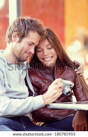 Happy young couple looking at pictures on camera. Beautiful young lovers having fun together outside looking at photos on vintage retro camera. Interracial couple, Asian woman, Caucasian man. - stock photo
