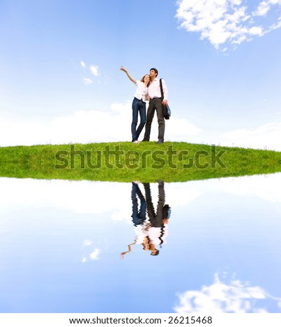 Happy young couple looking at something above a green meadow. - stock photo