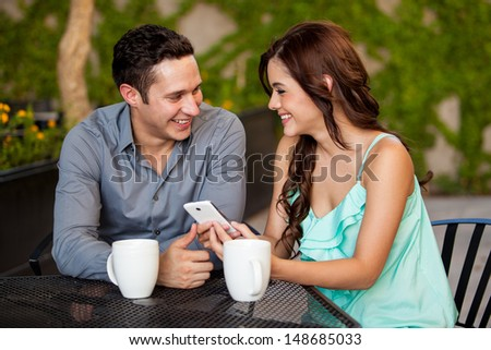 Happy young couple looking at something on a cell phone while having coffee at a restaurant - stock photo