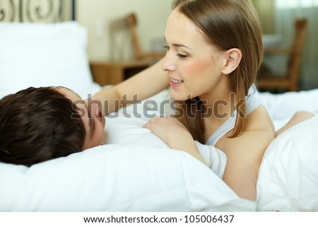 Happy young couple lying in bed and looking at one another - stock photo